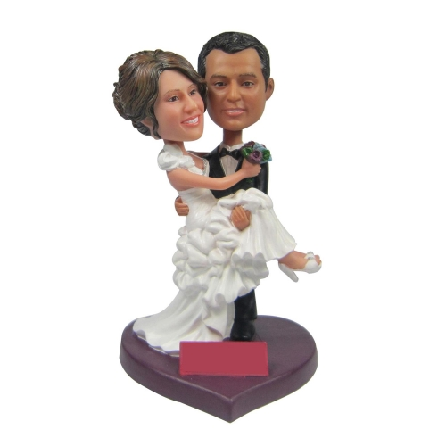 groom holding bride wedding cake topper